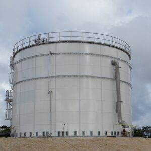 White Bolted Panel Storage Tank with large pipe and cloudy sky