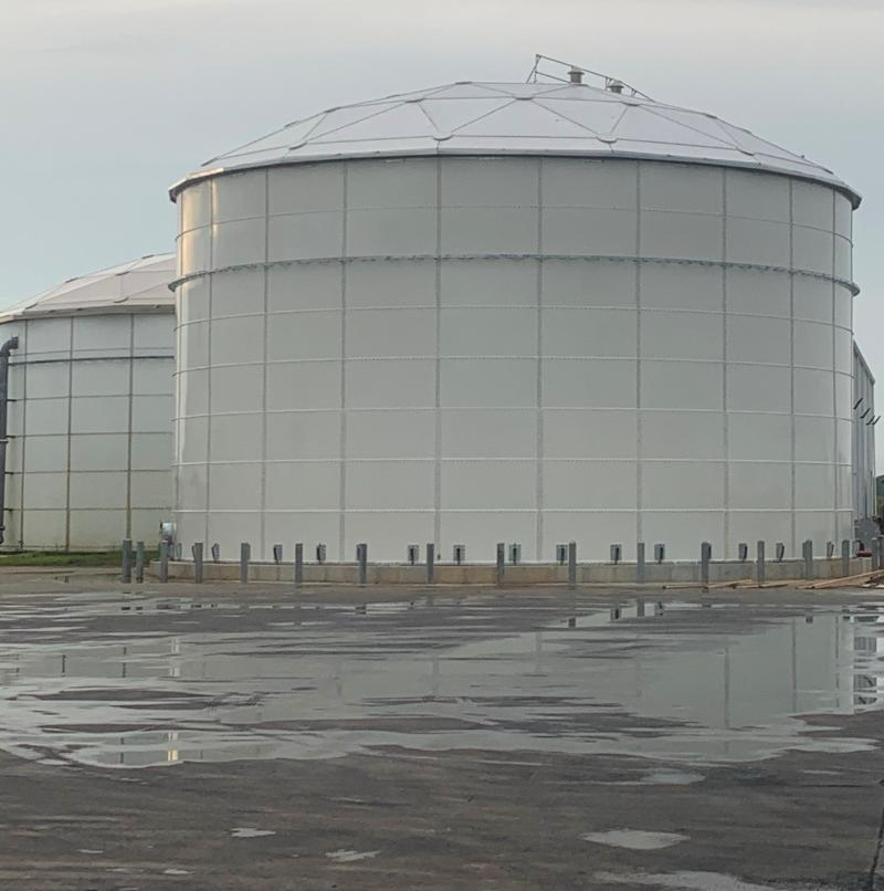 Two White Storage tanks with aluminum domes on a wet field