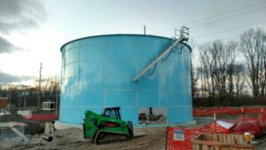 Light blue bolted tank with a stairwell being installed on the side. Small green bobcat in the front.