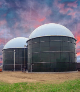 Two Glass Fused to Steel Biogas Storage tanks with white domes and sunset behind. Dirt field and grass in foreground.