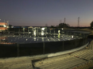 Worker installing perimeter of a glass lined steel tank at night. Dark blue tank, sunset and lights