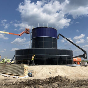 Dark blue Double Wall tank on a hill with construction equipment. Blue Sky with Clouds