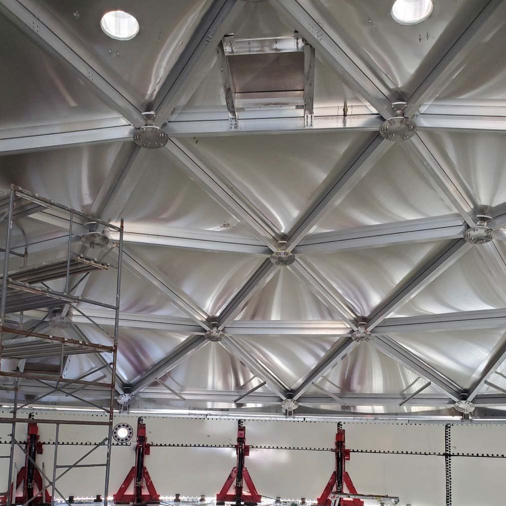 Inside a water storage tank looking at the aluminum dome room from below.