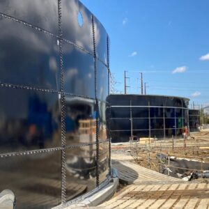 Three dark blue water storage tanks with wood planks in front of them