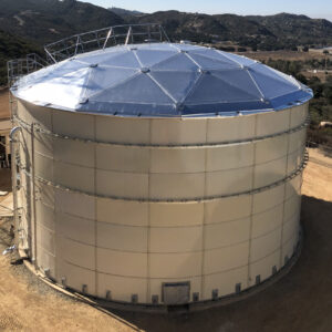 Beige bolted tank with an aluminum dome roof erected on a hill. Overflow pipe, ladder and manway. Mountains in the background