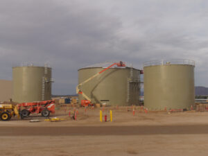 Three Green Bolted Storage Tanks with boom lift in foreground