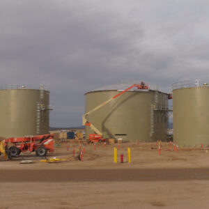 Three Beige Water Storage Tanks with Cloudy Gray Sky. Construction equipment in the foreground