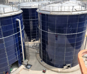 Cobalt blue water storage tanks with domes and safety rails