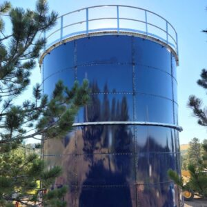 Blue water storage tank with safety rail. Pine trees in front