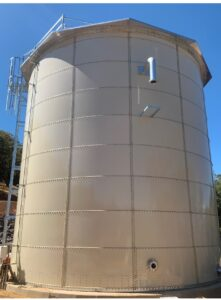 Sand colored water tank and safety cage against a blue sky