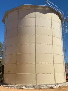 Tan colored bolted tank with ladder and railing
