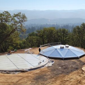 Tank floor and aluminum dome laying atop a dirt hill. Trees and mountains in the background. Blue Sky.
